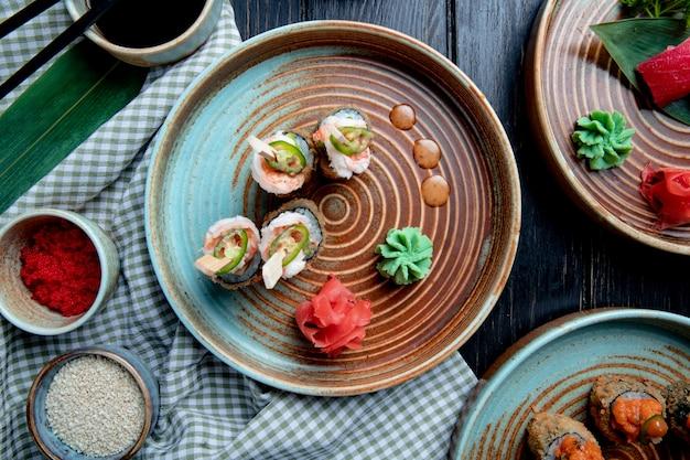 Widok z góry na zestaw pieczonych rolad sushi z krewetkami podawanymi z wasabi i imbirem na talerzu na drewnie