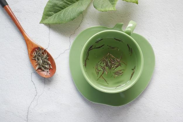 Widok z góry na zieloną herbatę i liść ziołowy w małej szklanej misce na stole