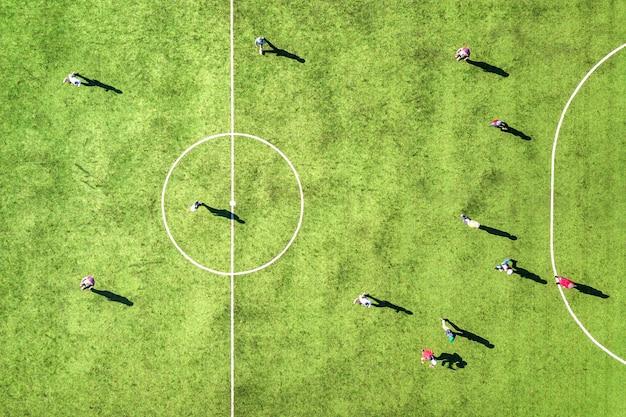 Widok z góry na zielone boisko do piłki nożnej i graczy grających w piłkę nożną. drone wykonał zdjęcie małych, nierozpoznawalnych sportowców na stadionie pokrytym trawą podczas zajęć sportowych.