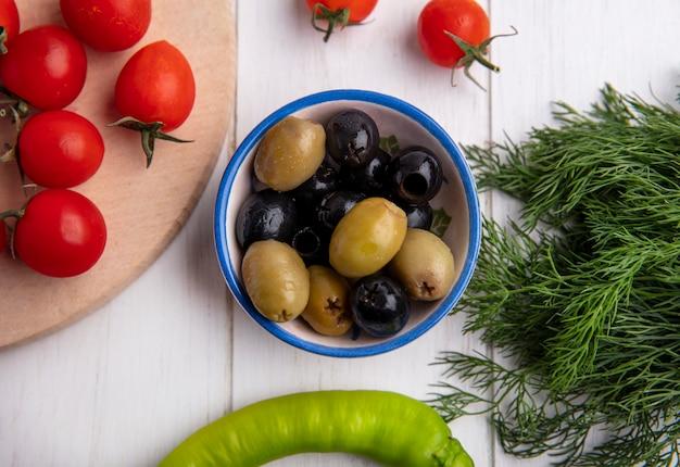 Widok z góry na zielone i czarne oliwki w misce i pomidory z koperkiem na powierzchni drewnianych