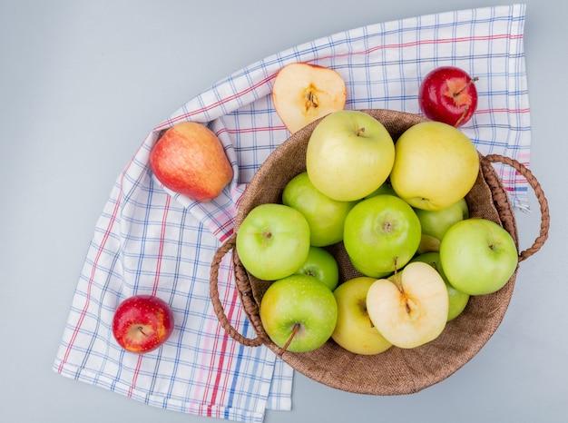 Widok z góry na zielone i żółte jabłka w koszu z czerwonymi na kraciastej tkaninie i szarym tle