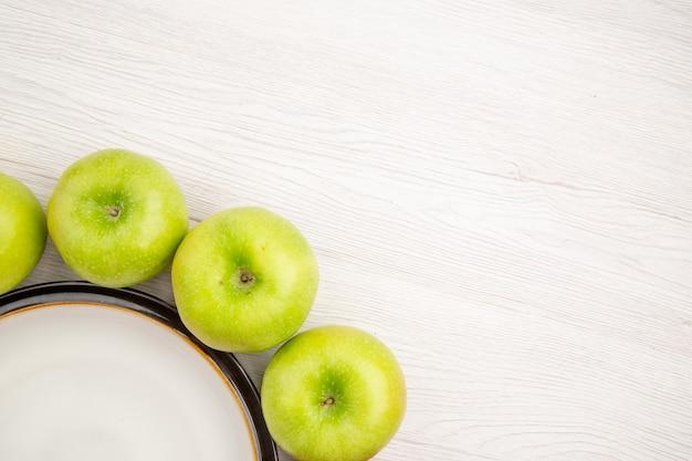 Widok z góry na zielone jabłka wokół okrągłego talerza na białym tle