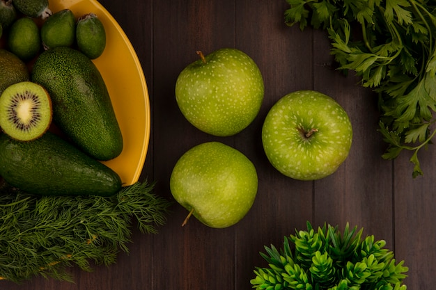 Widok z góry na zielone jabłka ze świeżymi owocami, takimi jak awokado feijoas i kiwi na żółtym talerzu na drewnianej ścianie