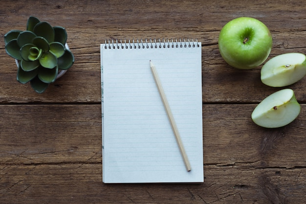 Widok z góry na zielone jabłko, notatnik i ołówek na podłoże drewniane