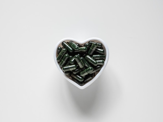 Widok z góry na zielone pigułki chlorelli w białej misce w kształcie serca na białym tle z miejscem na kopię