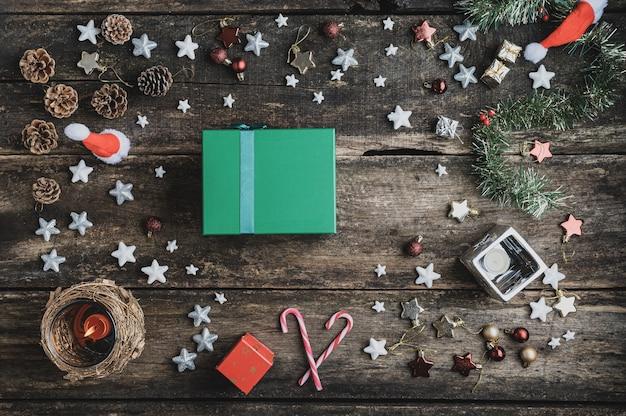 Widok z góry na zielone pudełko na prezenty świąteczne umieszczone na rustykalnym drewnianym biurku w centrum świątecznej oprawy wykonanej z ozdób i świec.