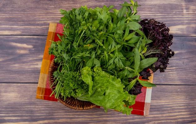 Widok z góry na zielone warzywa jak kolendra mięta bazylia sałata w koszu na szmatką na drewnie