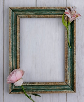 Widok z góry na zielonkawo-złotą ramkę z jasnoróżową różą i lilią na szarej powierzchni