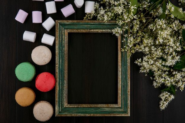 Widok z góry na zielonkawo-złotą ramkę z makaronikami marshmallows i kwiatami na czarnej powierzchni