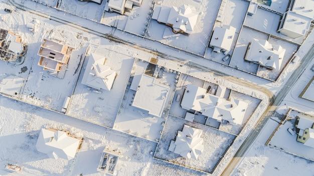 Widok z góry na zimową wioskę z ośnieżonych domów i dróg. widok z lotu ptaka na krajobraz