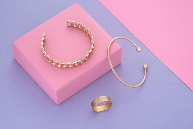 Widok z góry na złote bransoletki i pierścionek na pastelowych kolorach tła kopii przestrzeni