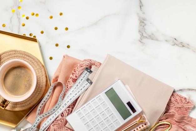 Widok z góry na złożone koronki i tkaniny jedwabne w kolorze koralowym ze szpulkami nici, kalkulator, notatnik, długopis, miara, nożyczki krawieckie przy filiżance kawy z ciasteczkami macarons na złotej tacy. skopiuj miejsce