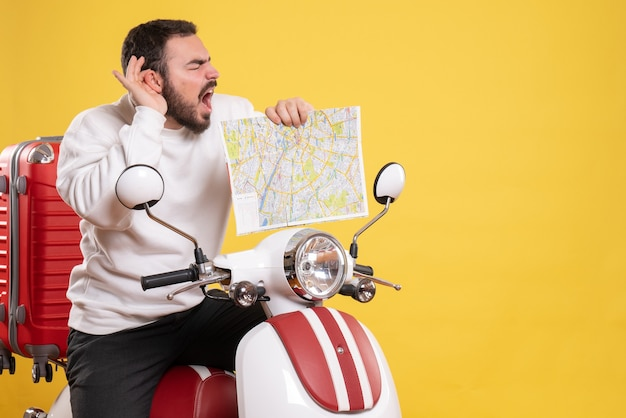 Widok z góry na zmartwionego mężczyznę siedzącego na motocyklu z walizką na nim, trzymającego mapę cierpiącą na ból ucha na izolowanym żółtym tle