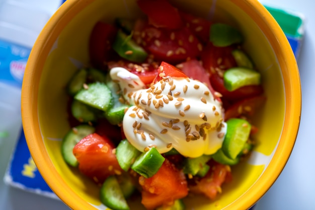 Widok z góry na żółtym talerzu z sałatką ze świeżych warzyw, ogórkiem z majonezem i ziarnem żyta