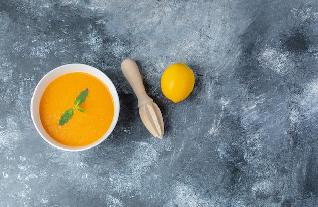 Widok z góry na zupę pomidorową i świeżą cytrynę z wyciskarką do cytryny.