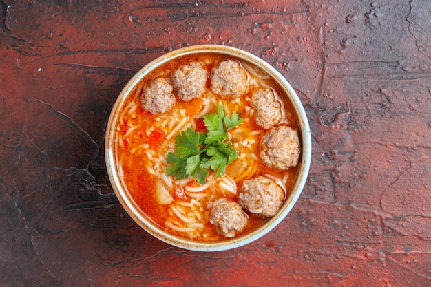 Widok z góry na zupę z klopsików z makaronem w brązowej misce na ciemnym tle