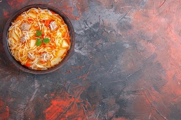Widok z góry na zupę z makaronem z kurczakiem w brązowej misce po prawej stronie ciemnego tła