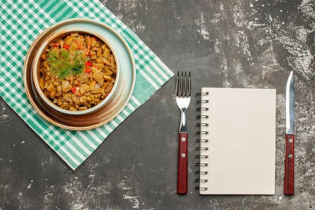 Widok z góry naczynie na obrusie biały zeszyt widelec nóż i talerz z apetyczną fasolką szparagową z pomidorami na desce na obrusie w kratkę na ciemnym stole