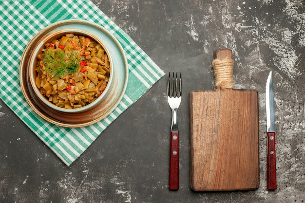 Widok z góry naczynie na obrusie drewniana deska do krojenia widelec nóż i talerz apetycznej fasolki szparagowej z pomidorami na obrusie w kratkę na ciemnym stole