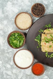 Widok z góry naczynie w talerzu gołąbki na talerzu obok miski z ziołami ryż kolorowymi przyprawami kwaśną śmietaną i czarnym pieprzem po prawej stronie szarego stołu