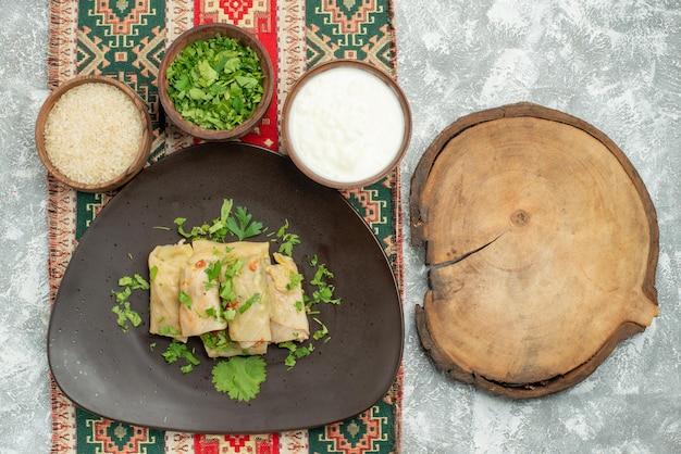 Widok z góry naczynie z ziołami szary talerz gołąbki kapusty ryż zioła kwaśna śmietana na kolorowym obrusie z wzorami po lewej stronie stołu obok deski do krojenia