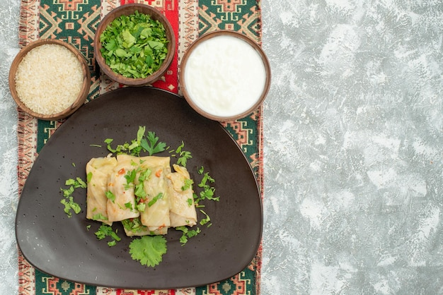 Widok z góry naczynie z ziołami szary talerz gołąbki kapusty ryż zioła kwaśna śmietana na kolorowym obrusie z wzorami po lewej stronie stołu