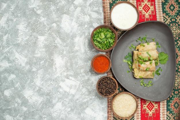 Widok z góry naczynie z ziołami talerz gołąbki i miskami ziół czarny papier przyprawy ryż i kwaśna śmietana na kolorowym obrusie z wzorami po prawej stronie stołu