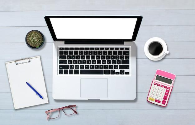 Widok z góry nad notebookiem na białej drewnianej podłodze w stylu biurowym.