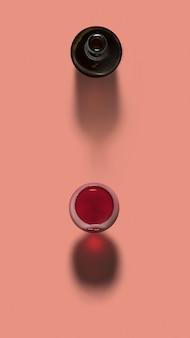 Widok z góry nad otwartą butelką i kieliszek czerwonego wina na pastelowym koralowym tle z miękkimi ciemnymi cieniami, miejsce na kopię