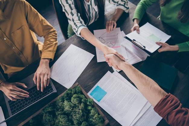 Widok z góry nad wysokim kątem, wykadrowany z odnoszących sukcesy partnerów biurka przy stole studenta, który ma rozmowę kwalifikacyjną