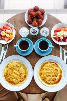 Widok z góry, nakrycie stołu, balijskie tropikalne śniadanie z owocami, kawą, jajecznicą i naleśnikiem bananowym