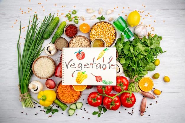 Widok z góry napis warzywny na spiralnym notatniku na świeżej żywności cytryna ziarna kukurydzy cytryna spadła butelka oleju miód na białym tle