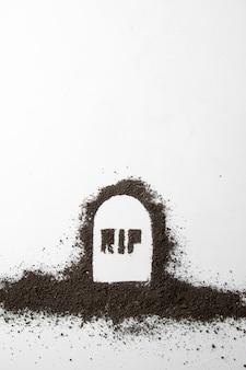 Widok z góry napisu rip na kształcie grobu z ciemną glebą na białej powierzchni