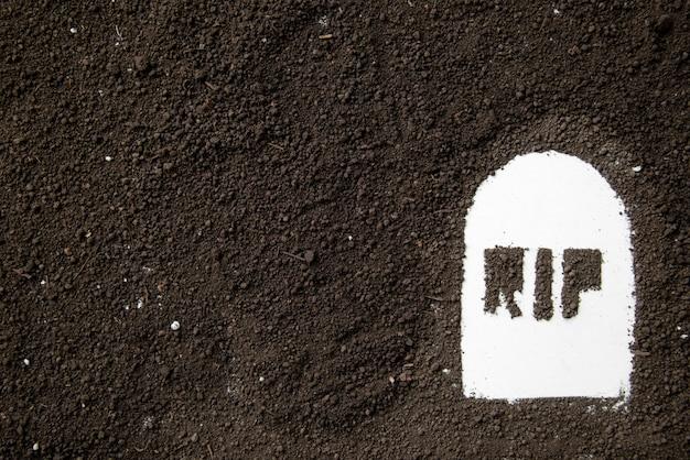 Widok z góry napisu rip na kształcie grobu z ciemną glebą