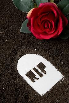 Widok z góry napisu rip z ciemną glebą i czerwonym kwiatem