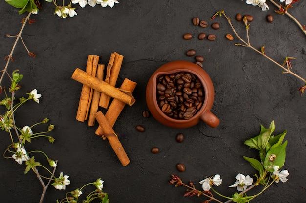 Widok z góry nasion kawy wraz z cynamonem na ciemności