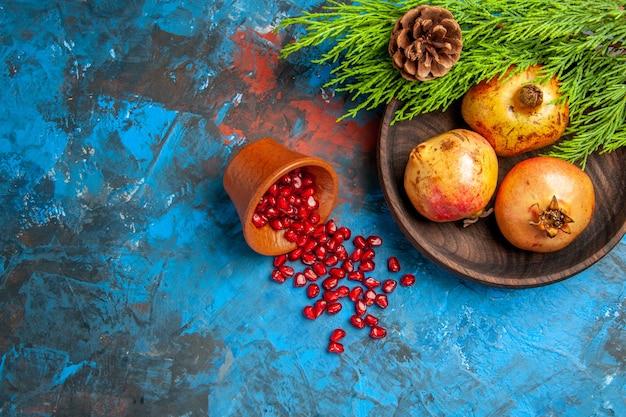 Widok z góry nasiona granatu umieszczone w drewnianym kubku z rozsypanymi nasionami granaty na drewnianym talerzu gałąź sosny na niebieskiej powierzchni