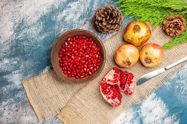 Widok z góry nasiona granatu w drewnianej misce nóż obiadowy granaty gałąź sosny na niebiesko-białej powierzchni