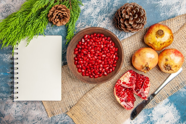 Widok z góry nasiona granatu w drewnianej misce nóż obiadowy granaty notatnik gałąź drzewa sosnowego i szyszki na niebiesko-białym tle
