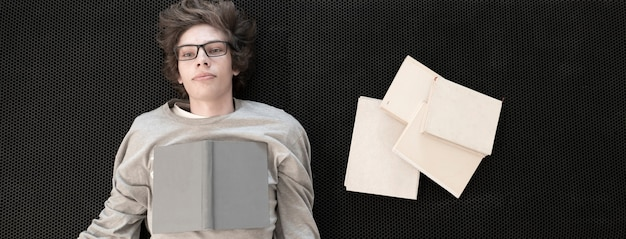 Widok z góry nastolatka chłopca leżącego na podłodze i czytania książek, uczenia się i studiowania