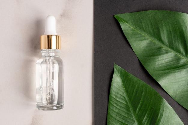 Widok z góry naturalnego olejku eterycznego, szklanej butelki z kroplami surowicy na marmurze