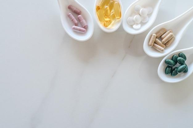 Widok z góry naturalnego suplementu witaminy na białej łyżce jako rama marmurowa ściana tekstur. koncepcja trendu zdrowego odżywiania.