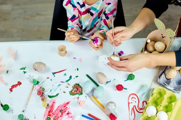 Widok z góry nie do poznania matka i jej córka w święta wielkanocne, kolorowanie pisanek. szczęśliwa rodzina przygotowuje się do wielkanocy.
