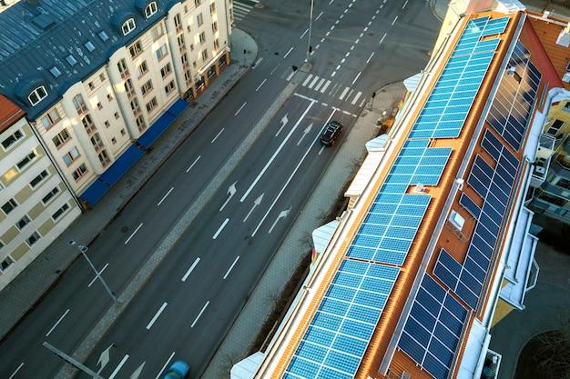 Widok z góry niebieski panel słoneczny fotowoltaiczny system na wysokim dachu budynku mieszkalnego na szczycie w słoneczny dzień. koncepcja produkcji ekologicznej zielonej energii odnawialnej.