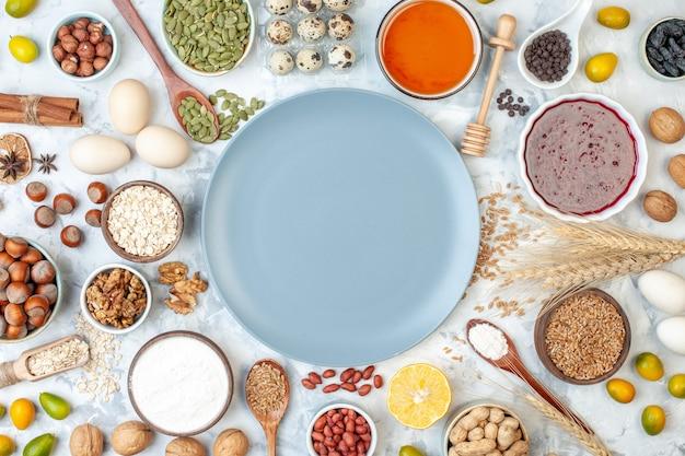 Widok z góry niebieski talerz z mąką galaretki jajka i różne orzechy na białych orzechach owocowych cukier zdjęcie słodkie ciasto ciasto kolor ciasto