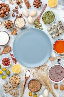 Widok z góry niebieski talerz z mąką galaretowatą jajkami i różnymi orzechami na białych orzechach owocowych cukier fotograficzny ciasto ciasto kolorowe ciasto