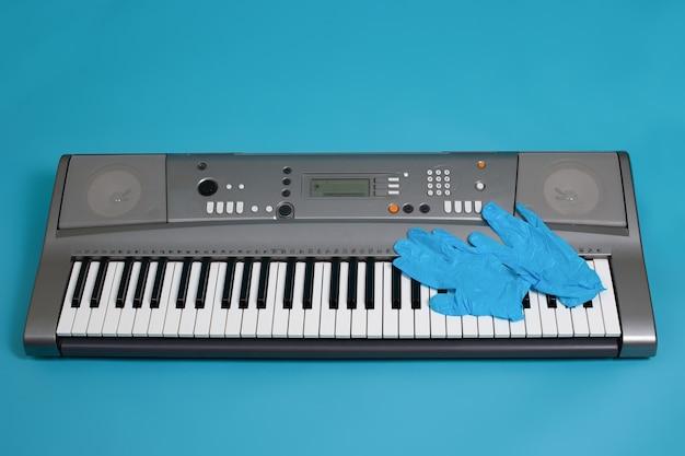 Widok z góry niebieskich rękawiczek medycznych na klawiszach szarego elektronicznego syntezatora