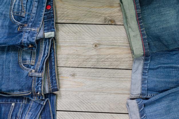 Widok z góry niebieskie dżinsowe ułożone na drewniane. koncepcja odzieży uroda i moda