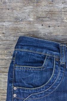 Widok z góry niebieskie dżinsy na drewnianym tle, leżał płasko. modne ubrania.