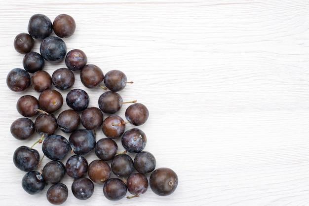 Widok z góry niebieskie śliwki okrągłe uformowane na jasnym tle owoce łagodny kwaśny soczysty